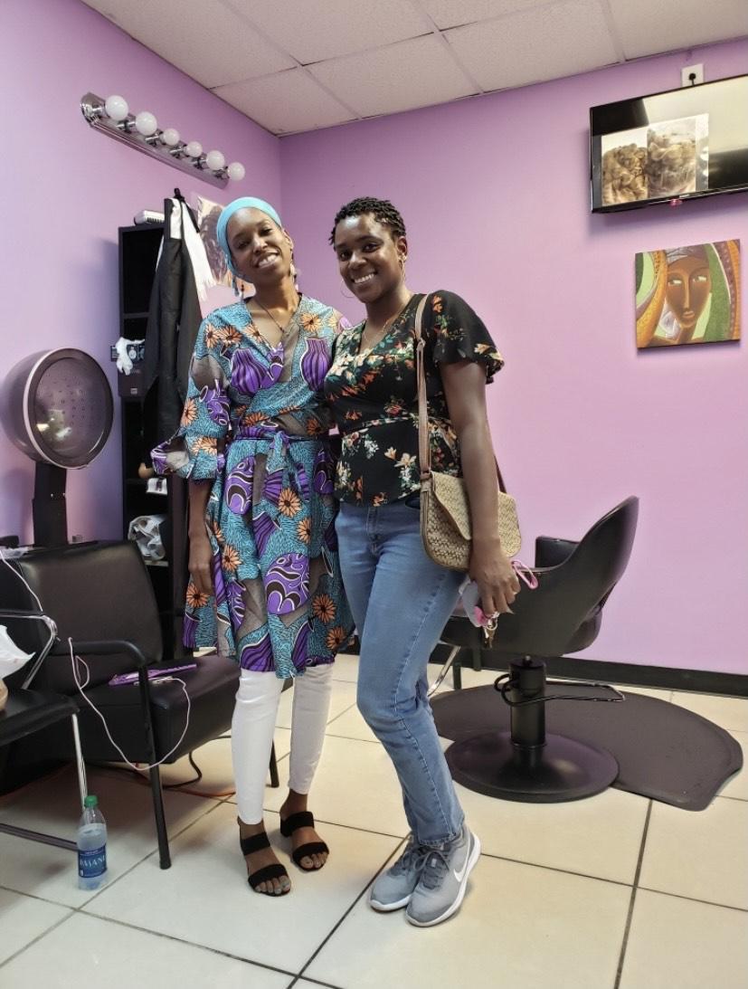 Kareemah Hanifa, left, stands with a patron of her Marietta hair salon in 2019.