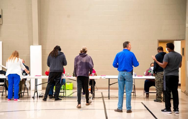 Voters stand in line inside a polling location.