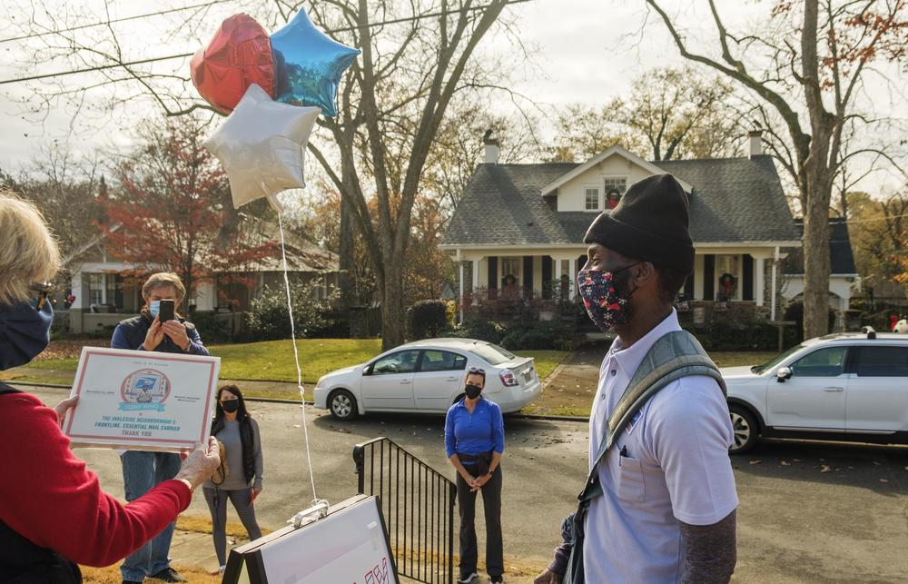 """Macon postal carrier Tony King, right, as Susan Cable, left, reads a declaration of """"Tony King Day"""" for the Ingleside neighborhood Monday. King has carried mail for 20 years in the neighborhood and has been working over time during this pandemic holiday season."""