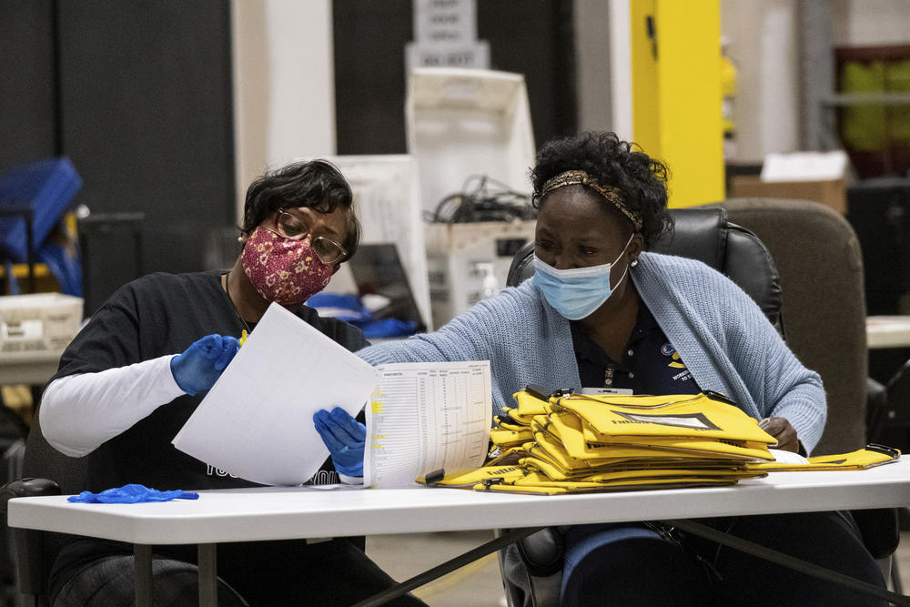Two women sit at a table looking at a pile of ballots.