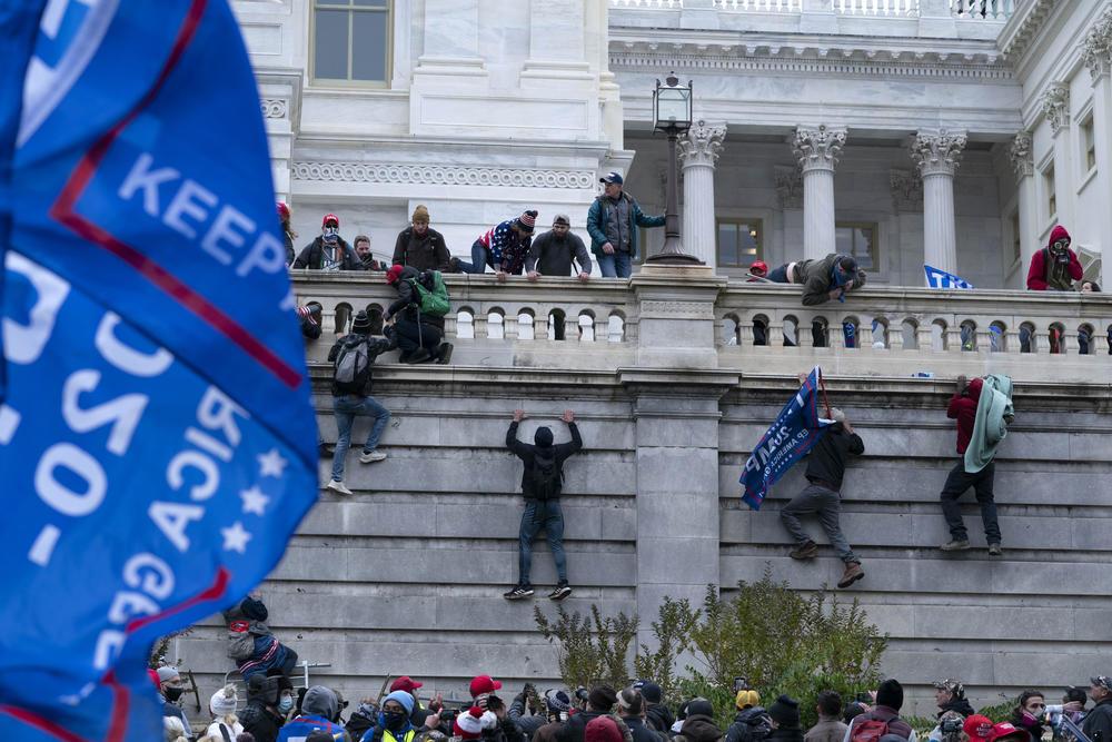A mob scales the walls at the U.S. capitol.