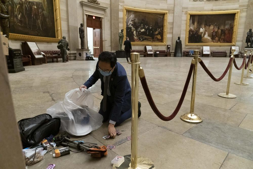 A man in a suit and tie picks up pieces of trash from the floor of the rotunda.