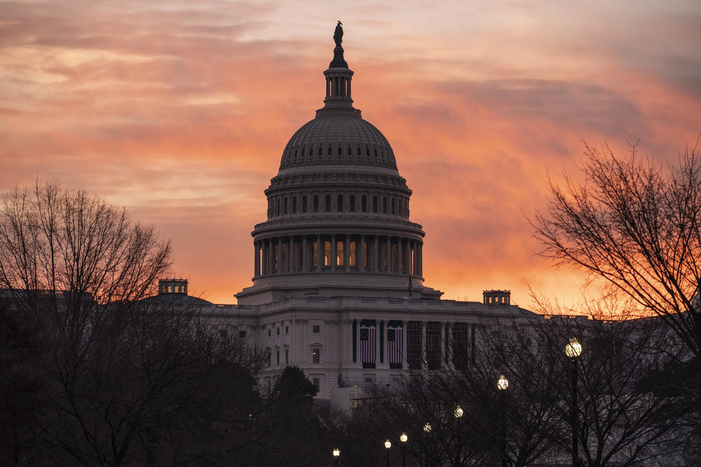 The U.S. Capitol stands silhouetted by the rising sun in the dawn.