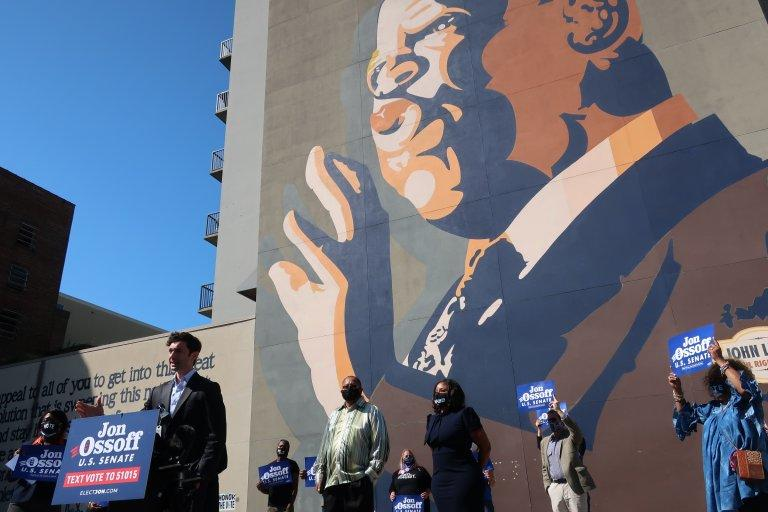 U.S. Senate candidate Jon Ossoff speaks to reporters in front of a mural in downtown Atlanta paying tribute to the late U.S. Congressman John Lewis, who backed Ossoff before his death.