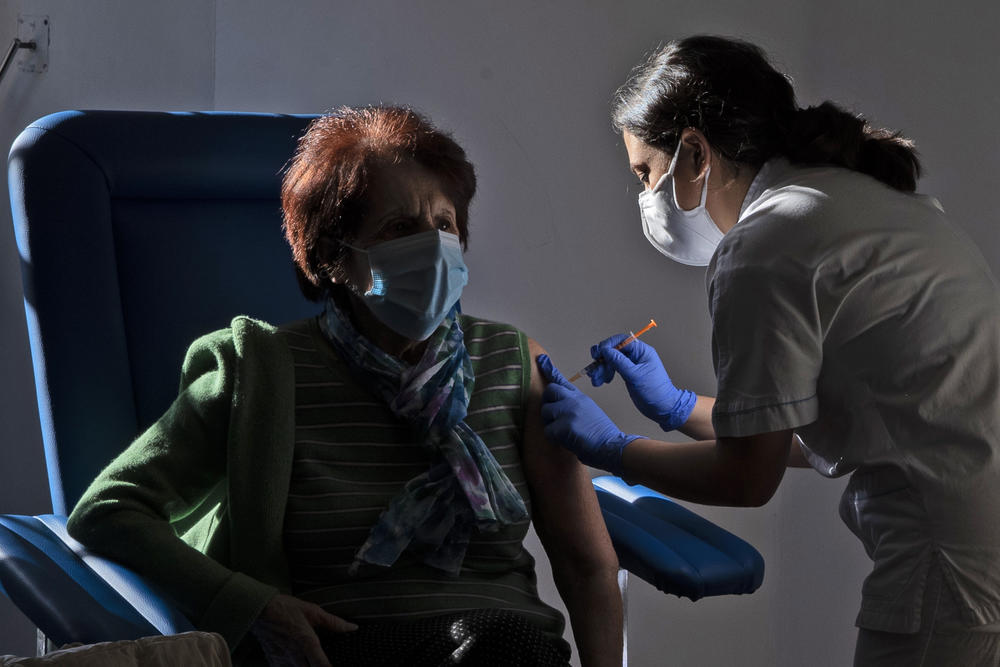 An older women receives a vaccine shot from a medical professional.