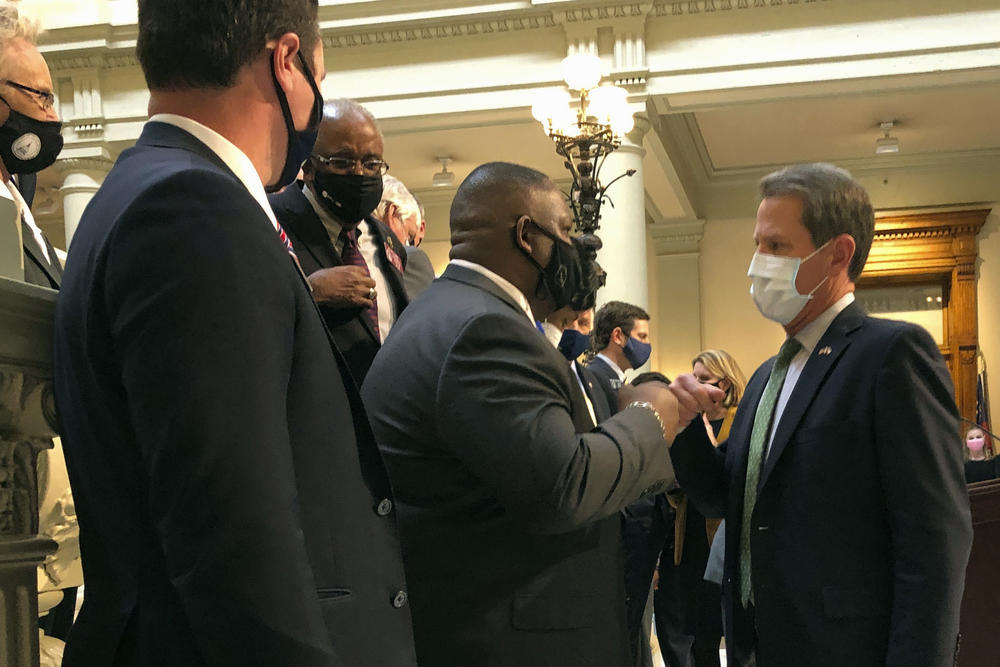 Governor Brian Kemp shakes hands with lawmakers.