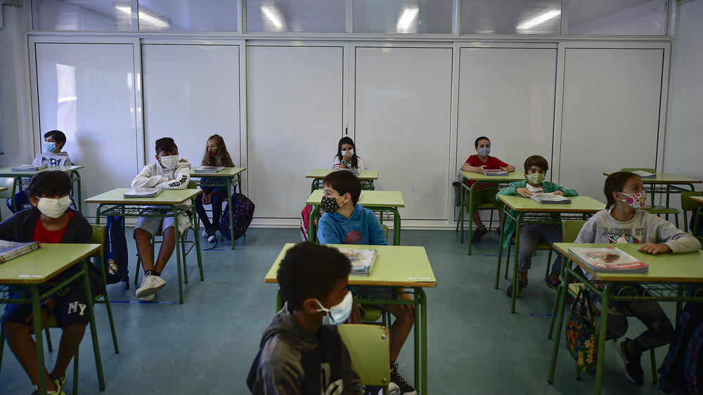 Students sit at rows of desks in a classrooms.