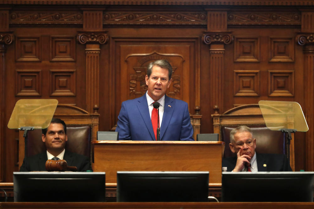Governor Brian Kemp stands at a lecturn in the General Assembly between David Ralston and Kyle Duncan.