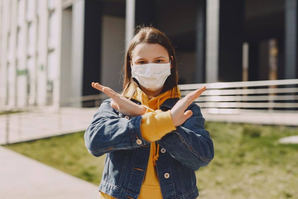 A girl in a face mask shows the sign for stop.