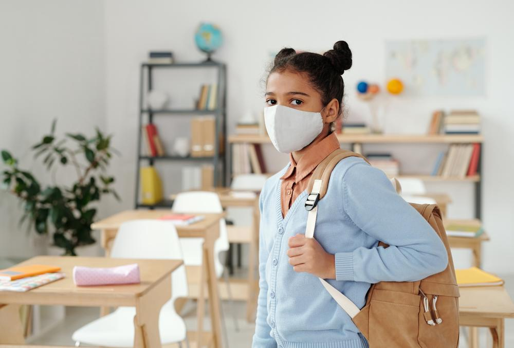 A girl with a backpack wearing a mask