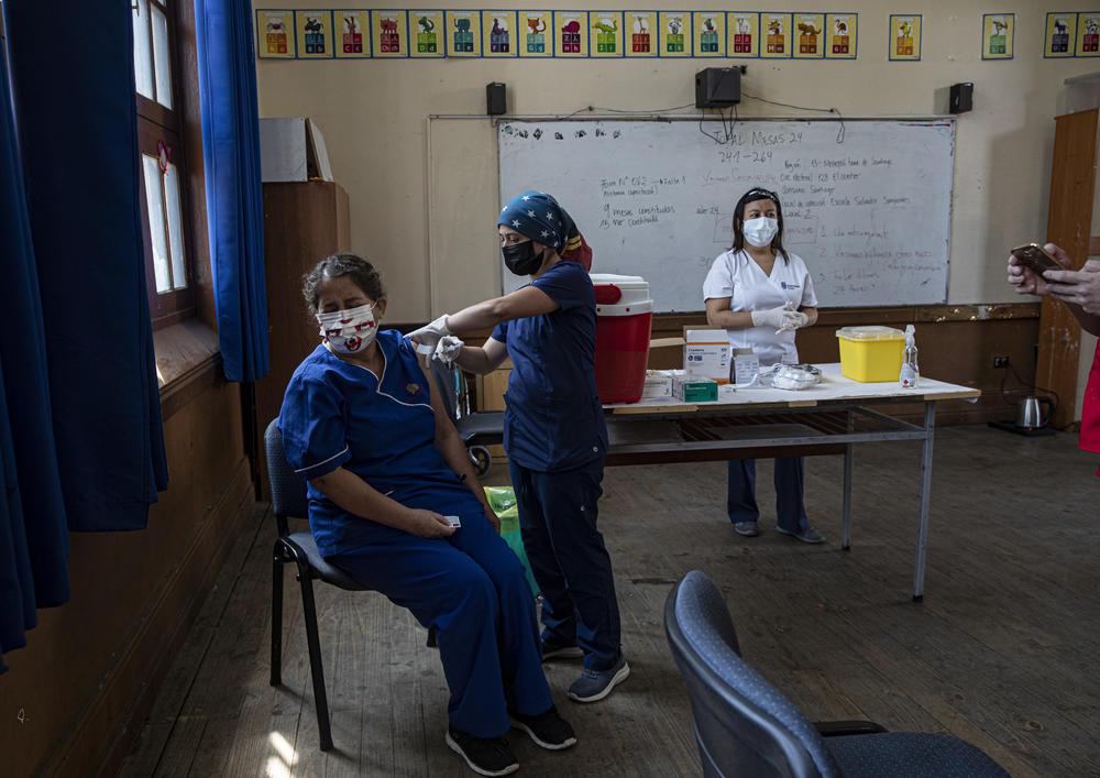 A teacher receieves a COVID-19 vaccine in a classroom in Santiago, Chile.
