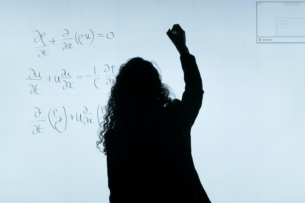 A backlit woman writes on a whiteboard