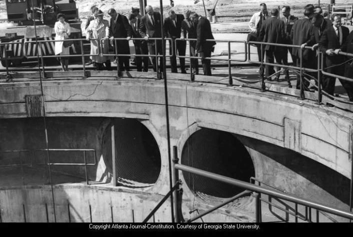 Visitors to Thiokol in 1964 look down into depths of giant static firing pit which is 120 feet deep. The pit was originally used to test rockets for space travel.