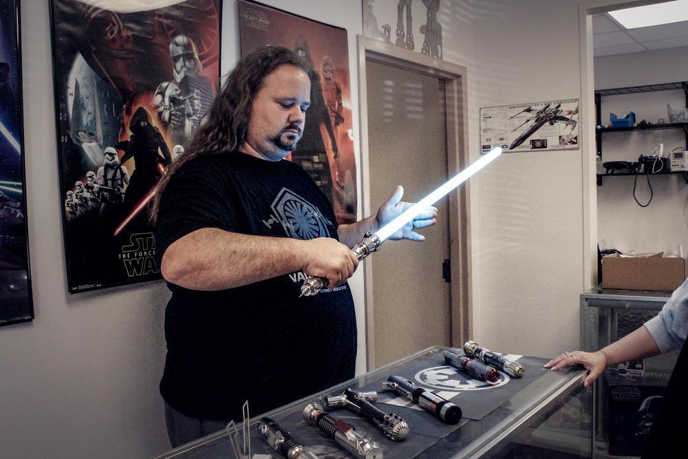 Co-owner Alan Johnson demonstrates one of Vader Vault's lightsabers.