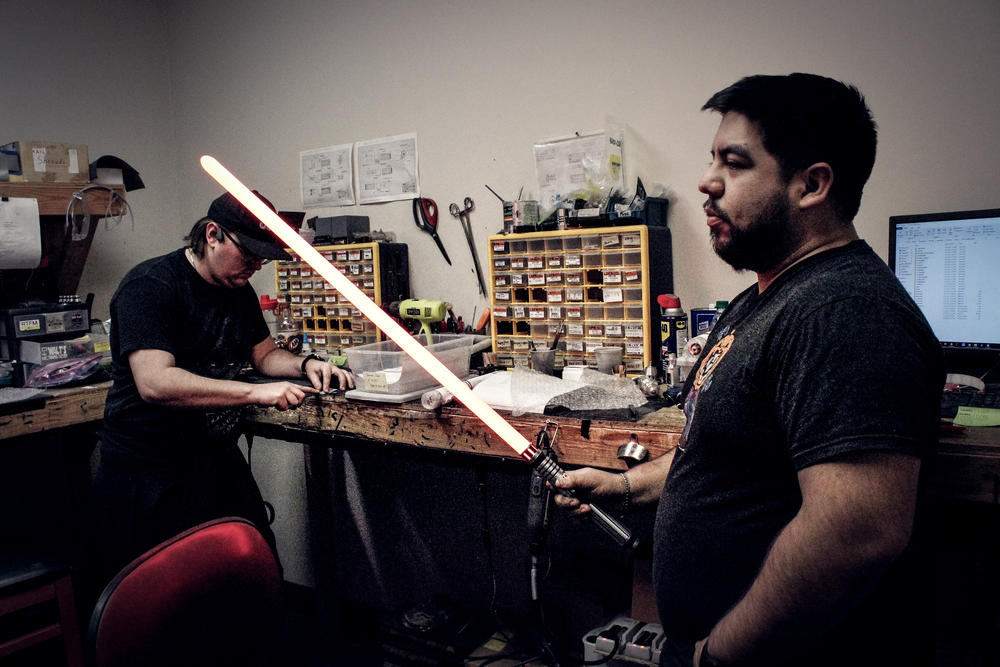 Vader's Vault employees test lightsabers in their workshop.