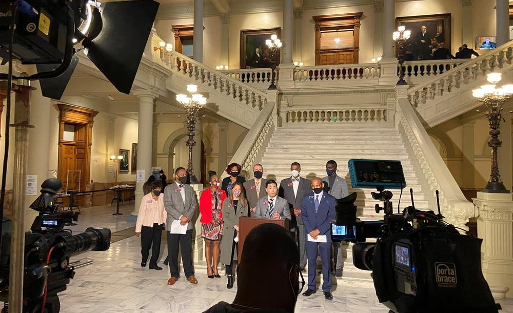 A group of lawmakers stand in the General Assembly addressing press during a news conference.
