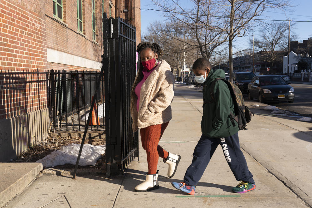 A woman walks her son into a school building.