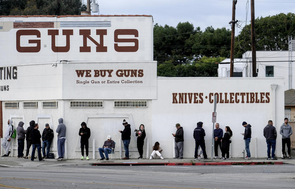 Folks stand in a line outside of a store selling guns.