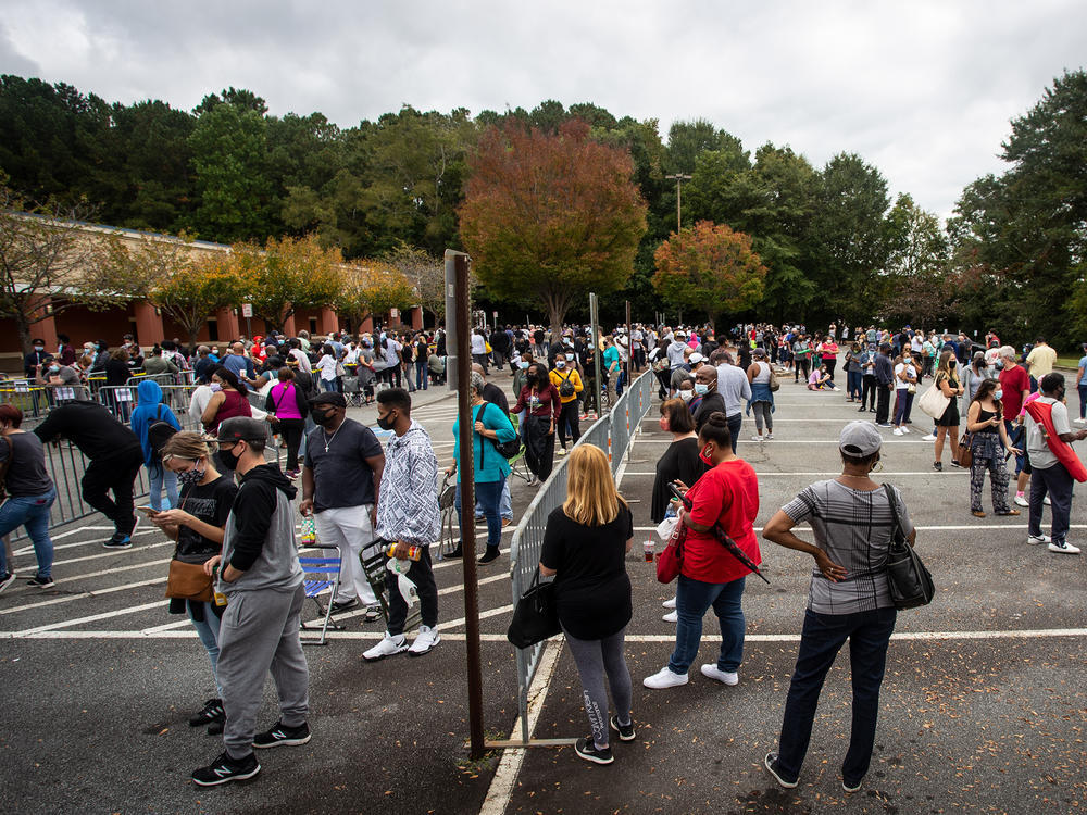 Hundreds of people wait in line for early voting on Monday, Oct. 12, 2020, in Marietta, Georgia. Eager voters have waited six hours or more in the former Republican stronghold of Cobb County, and lines have wrapped around buildings in solidly Democratic DeKalb County.
