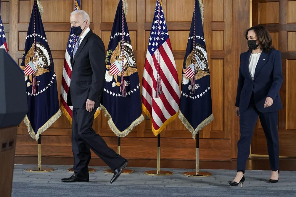 President Joe Biden and Kamala Harris walk together on a stage by American flags.