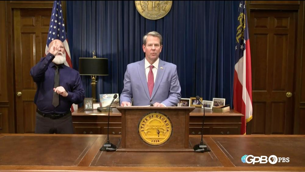 Governor Brian Kemp stands in the general assembly speaking to a camera.