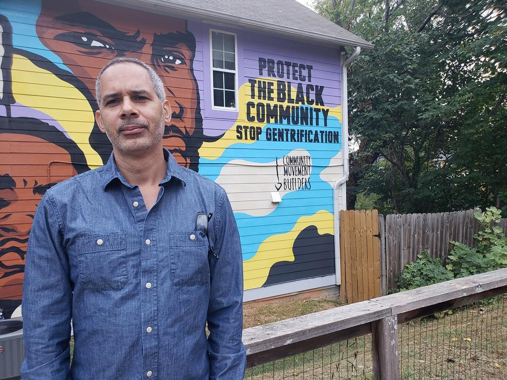 Kamau Franklin stands in front of his mural that says protect the Black community, stop gentrification.
