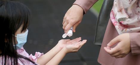 Child getting hand sanitizer