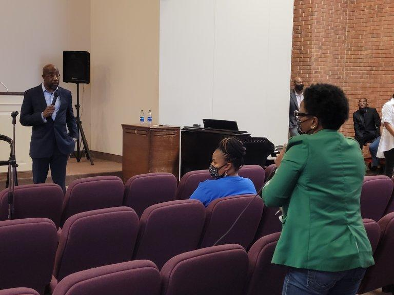 Sen. Raphael Warnock answers questions about federal aid from mothers Friday at Jackson Memorial Church in Atlanta.