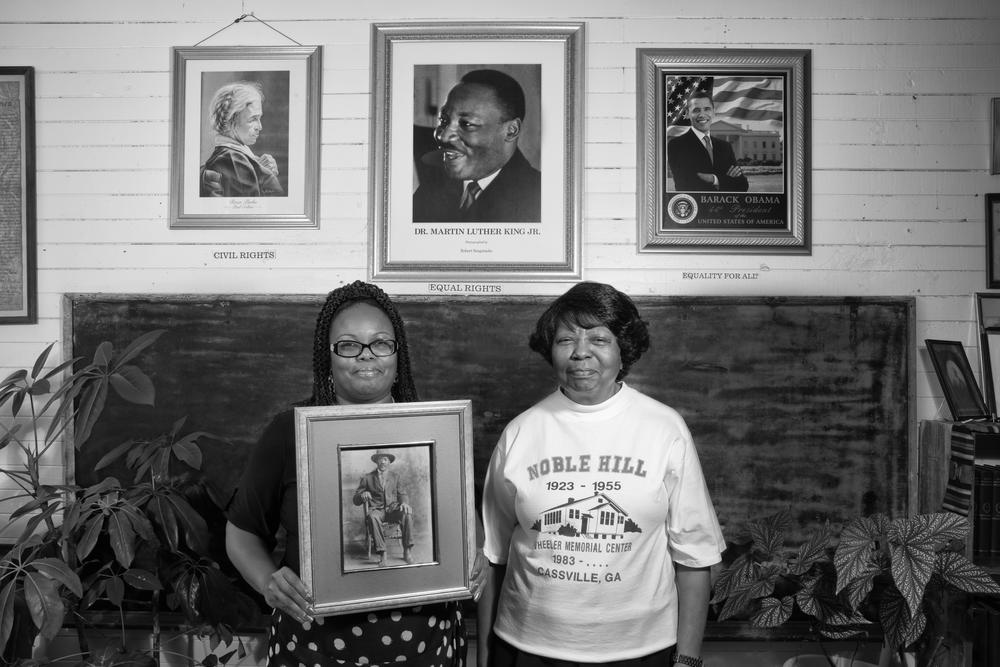Two women stand in a Rosenwald school holding history artifacts from the school's history.