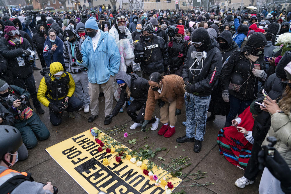 Flowers are placed on a banner as demonstrators gather outside the Brooklyn Center Police Department on Tuesday, April 13, 2021.