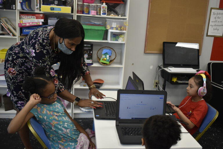 Daycare owner Shenette Zachary helps students get connected during online learning. Zachary is hoping federal funds will help her pay staff as enrollment levels continue to recover from the pandemic.