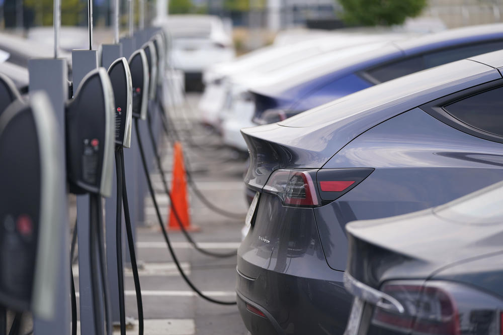 a lineup of Teslas plugged into charging stations