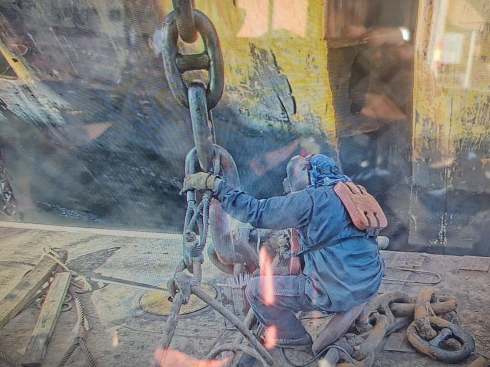 a worker handling a massive cutting chain