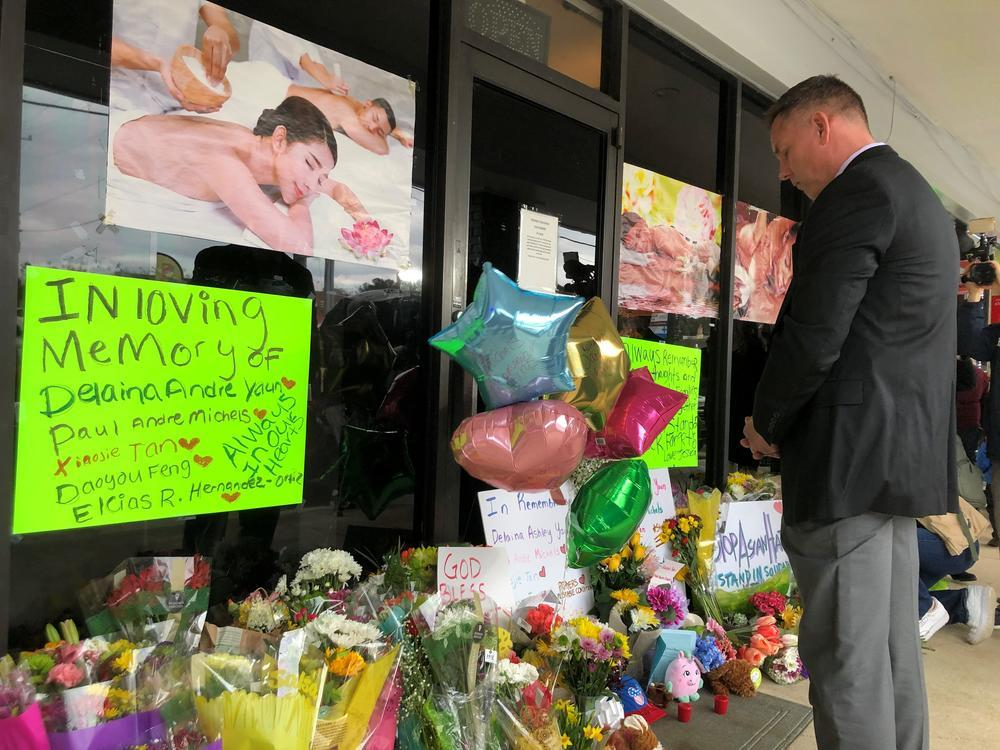 Cherokee County Sheriff Frank Reynolds bows his head after placing a bouquet of flowers outside Young's Asian Massage in Acworth, Ga., on Thursday, March 18, 2021.