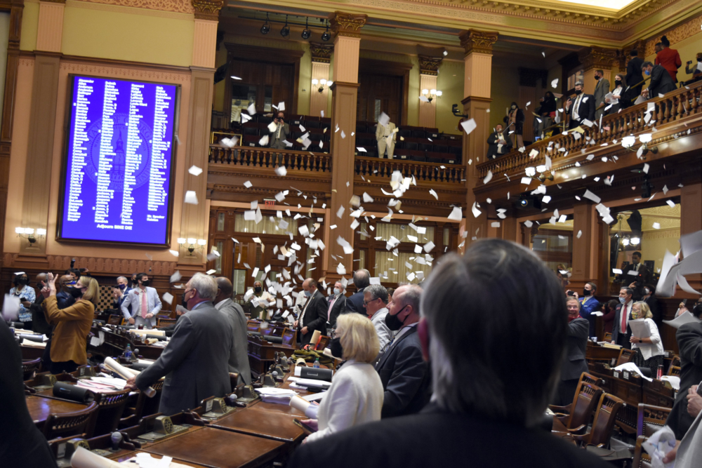 Lawmakers through paper in the air at the end of session.