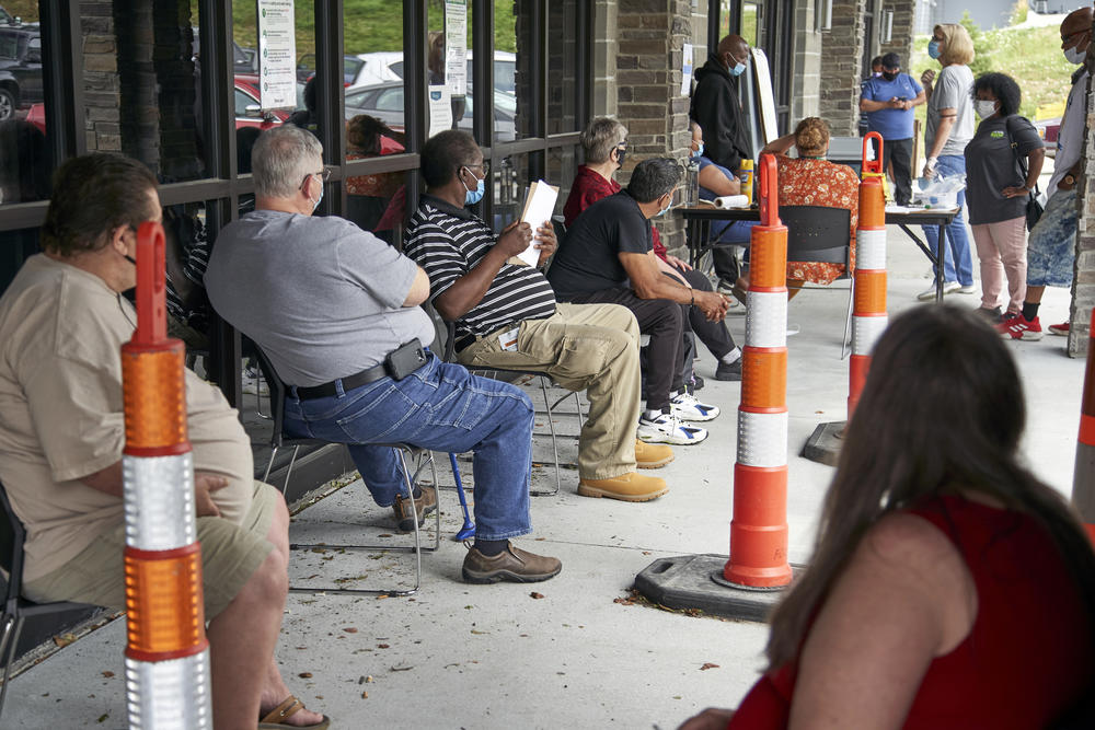 A group of people sit in line.