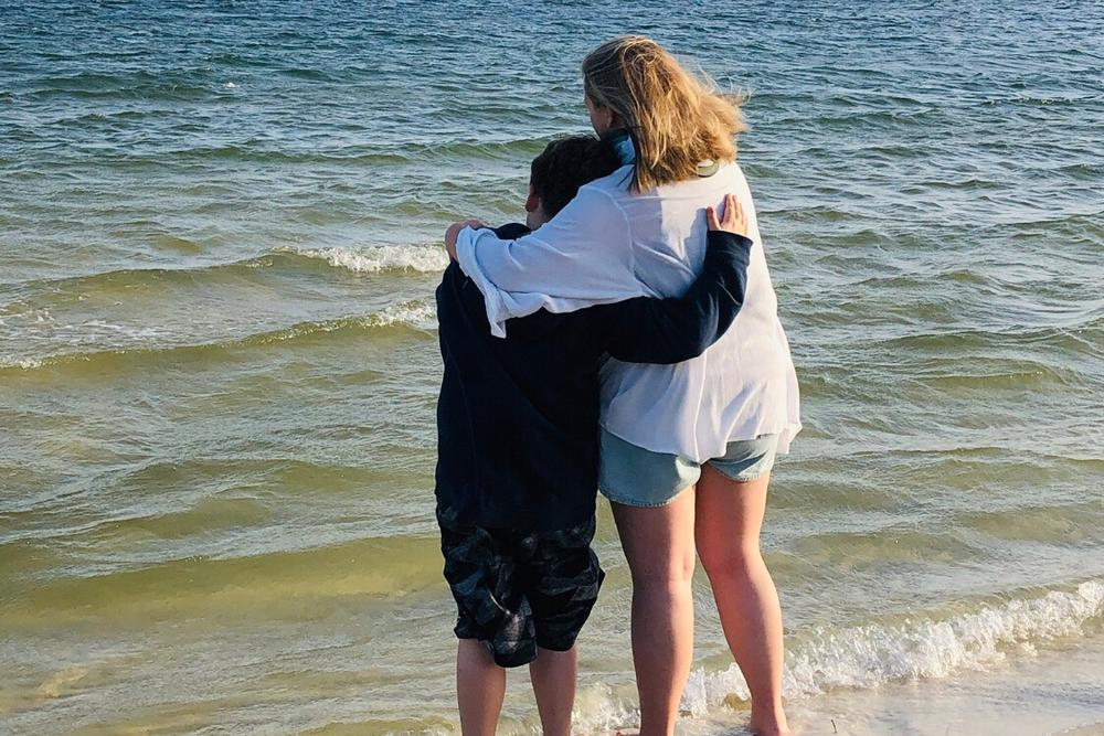 Brandon Little and his sister, Kylee, stand on a shore looking over waves.