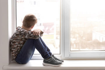 Kid sitting in window