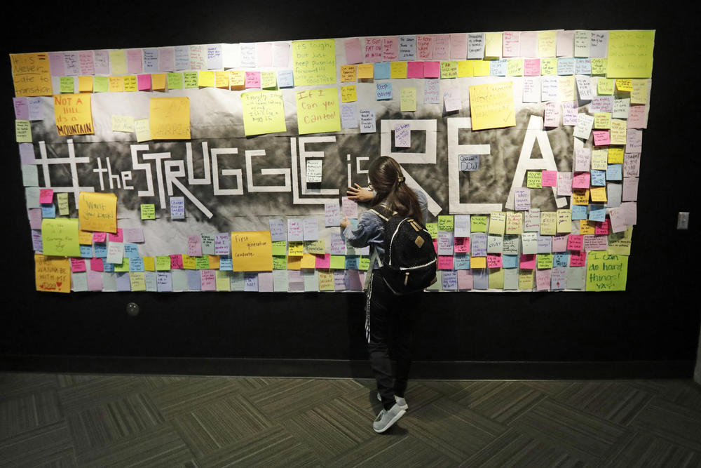 In this Nov. 14, 2019, photo, a student attaches a note to the Resilience Project board on the campus of Utah Valley University, in Orem, Utah.