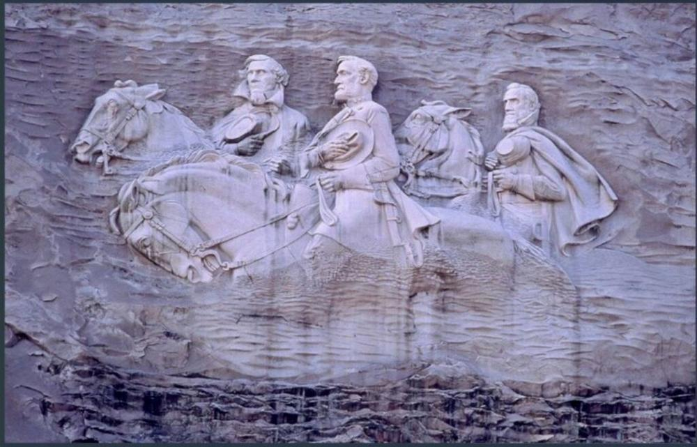"""Left to right: Confederate President Jefferson Davis and Confederate Generals Robert E. Lee and Thomas """"Stonewall"""" Jackson are carved into the side of Stone Mountain."""
