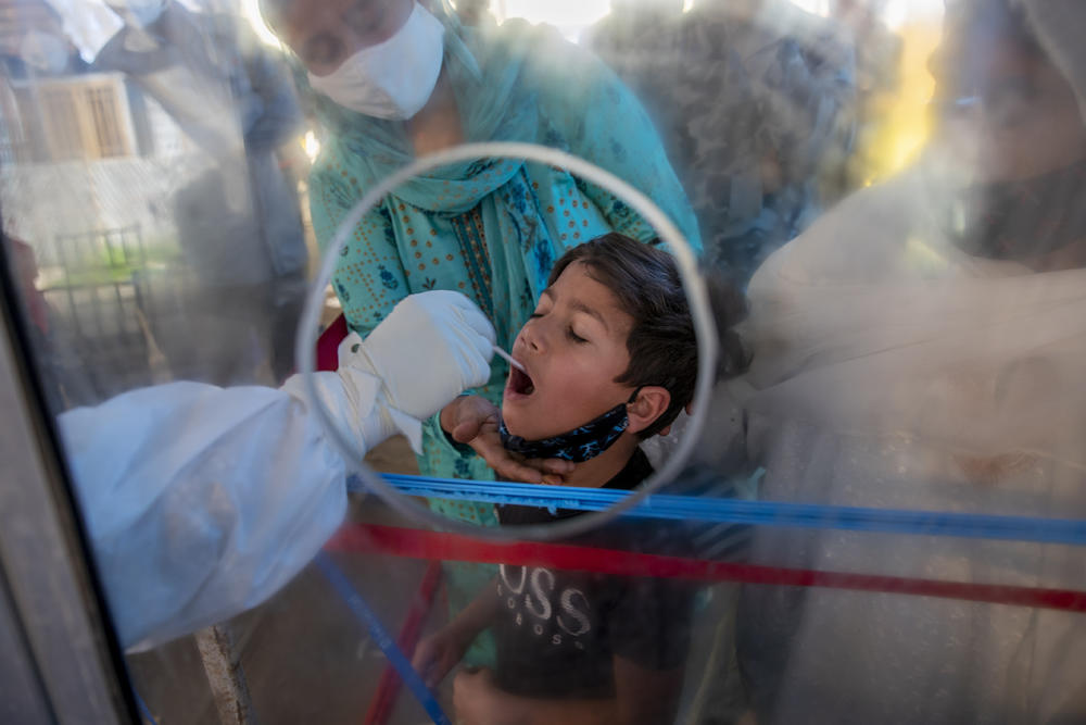 A boy in India is tested for COVID-19 through a plastic screen.