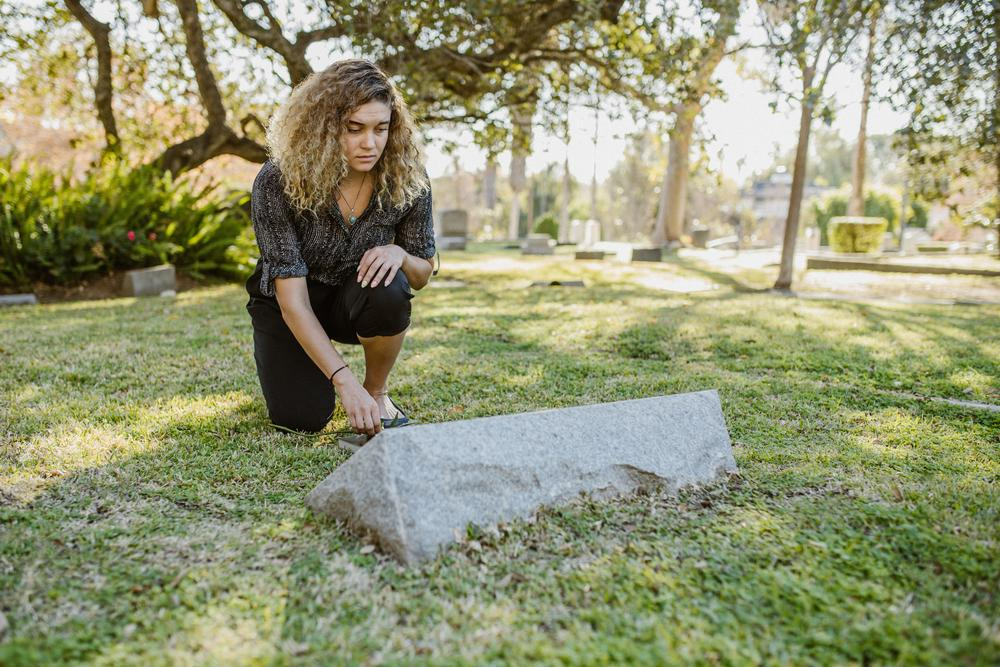 A woman kneels at a grave
