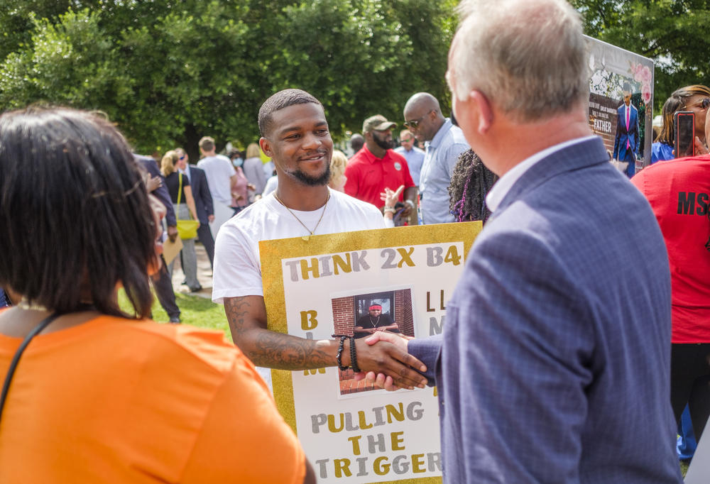 Shandarius Hillman shakes hands with Macon-Bibb County Mayor Lester Miller after Miller made public a plan to push back against rising rates of killing the city. Hillman's brother was killed in May.