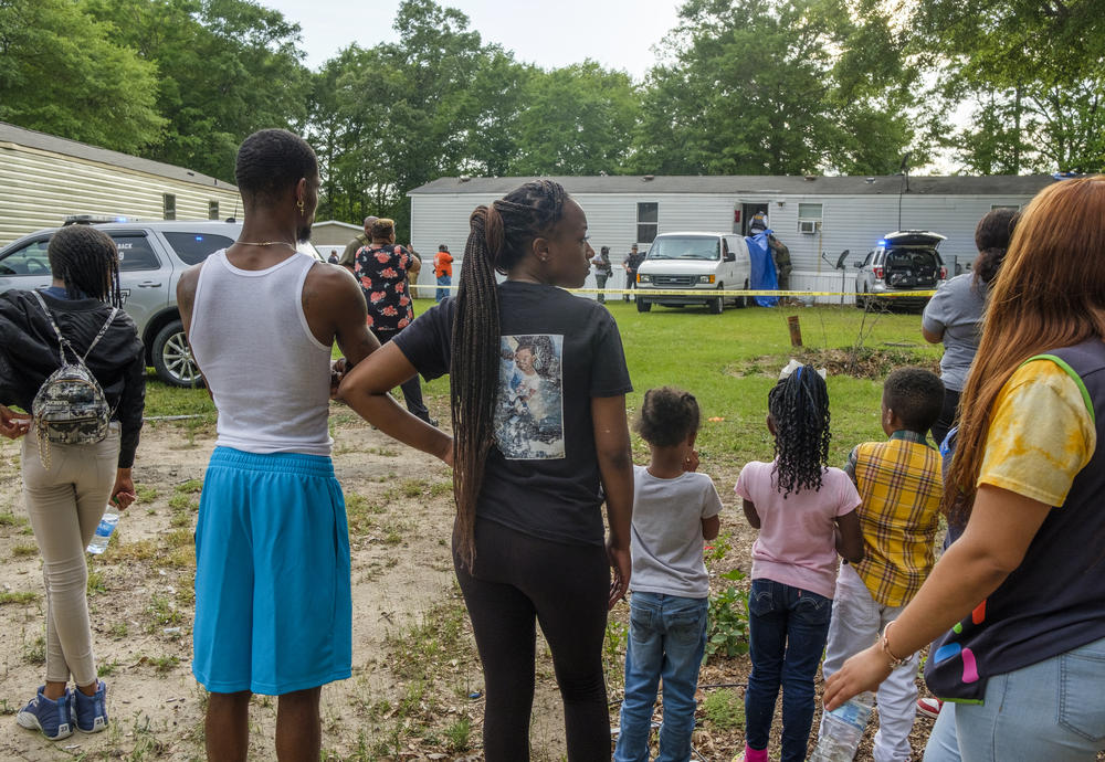 Family and neighbors of Quinterious Hillman and Jerod Lester watch as Bibb County Sheriff's Deputies investigate the scene of Hillman and Lester's killing in May.