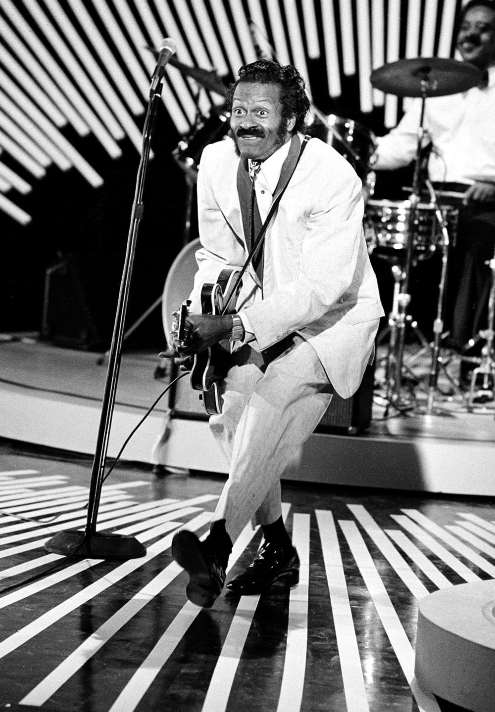 """American guitarist and singer Chuck Berry performs his """"duck walk"""" on stage as he plays his guitar on April 4, 1980. The location is not known."""