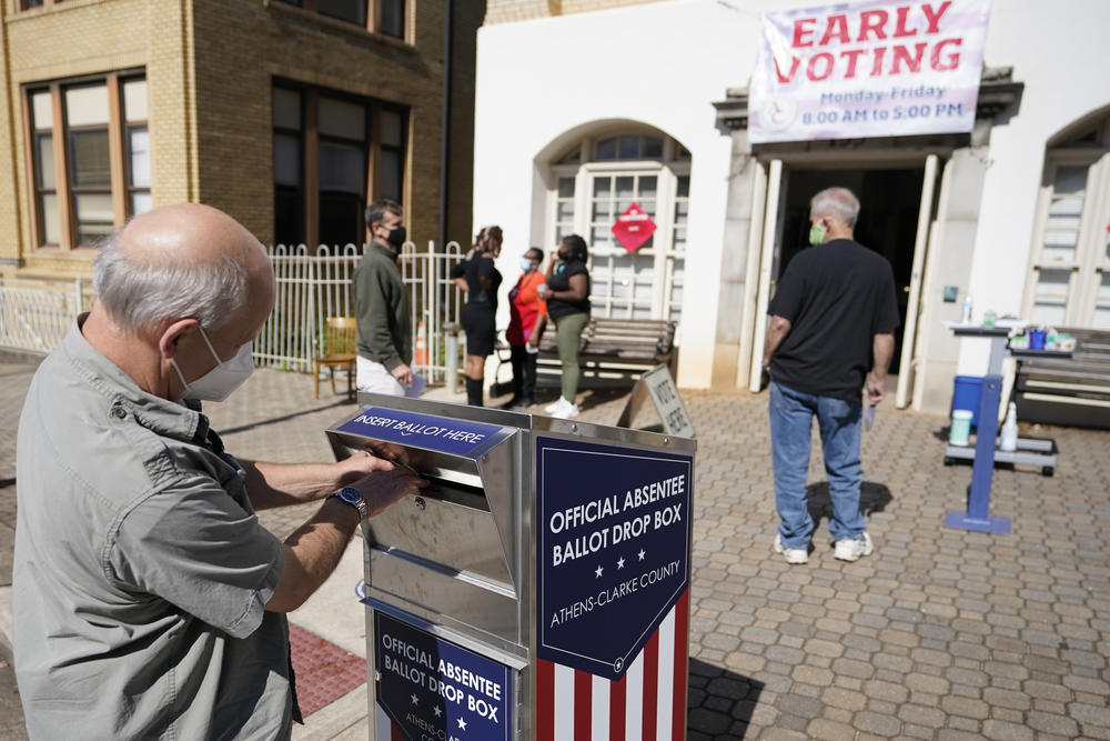 In this Monday, Oct. 19, 2020 file photo, a voter submits a ballot in an official drop box during early voting in Athens, Ga. Georgia's secretary of state says, Tuesday, June 15, 2021, his office is reviewing the handling of paperwork related to ballot drop boxes in the state's most populous county during last year's election.