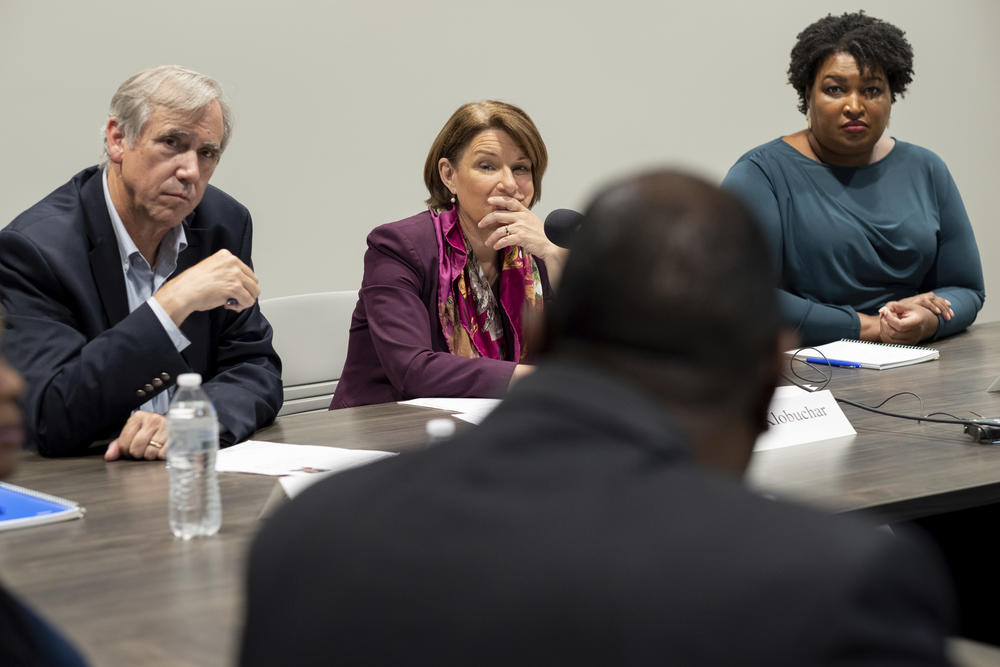 Sen. Jeff Merkley, left, D-Ore.; Sen. Amy Klobuchar, D-Minn., and former Georgia state Rep. Stacey Abrams, right, listen to people talk about their experiences in voting, in Smyrna, Ga., Sunday, July 18, 2021. (AP Photo/Ben Gray)
