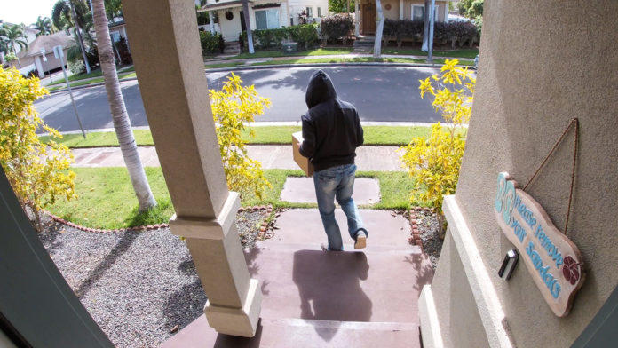 Unidentified person takes a package from a porch
