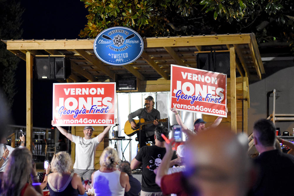 Vernon Jones supporters hold signs while country music star Travis Tritt performs at a fundraiser for the GOP gubernatorial candidate.