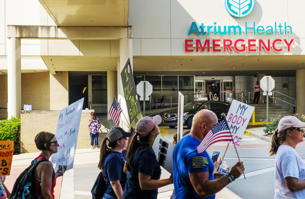 Protesters against the vaccine mandate for employees of the Medical Center at Atrium Health in Macon march by the hospital emergency room entrance on Saturday, August 14. Only a fraction of the about 100 protesters were Medical Center employees.